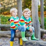 Deux garçons de petit enfant ayant l'amusement sur le terrain de jeu d'automne Photos libres de droits