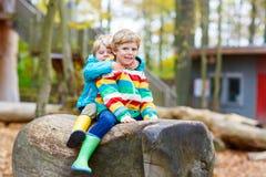 Deux garçons de petit enfant ayant l'amusement sur le terrain de jeu d'automne Image libre de droits