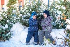 Deux garçons de petit enfant dans des vêtements colorés jouant dehors pendant les chutes de neige Loisirs actifs avec des enfants Photographie stock libre de droits