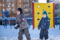 Deux garçons de petit enfant dans des vêtements colorés jouant dehors pendant les chutes de neige Loisirs actifs avec des enfants Photo stock