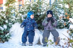 Deux garçons de petit enfant dans des vêtements colorés jouant dehors pendant les chutes de neige Loisirs actifs avec des enfants Photo libre de droits