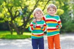 Deux garçons de petit enfant dans l'habillement coloré marchant main dans la main Image libre de droits