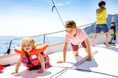 Deux garçons de petit enfant et fille d'enfant en bas âge appréciant le voyage de bateau à voile Vacances de famille sur l'oc?an  photos libres de droits