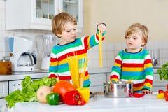 Deux garçons de petit enfant faisant cuire des pâtes avec des légumes Image libre de droits