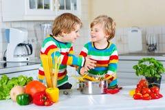 Deux garçons de petit enfant faisant cuire des pâtes avec des légumes Image stock