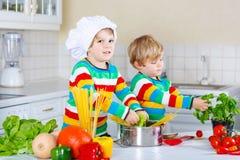 Deux garçons de petit enfant faisant cuire des pâtes avec des légumes Photos stock