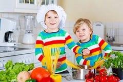 Deux garçons de petit enfant faisant cuire des pâtes avec des légumes Images libres de droits