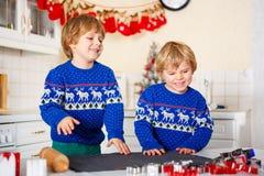 Deux garçons de petit enfant faisant des biscuits cuire au four de pain d'épice Photo libre de droits