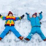 Deux garçons de petit enfant faisant l'ange de neige en hiver, dehors Photos libres de droits