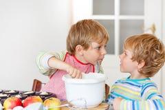 Deux garçons de petit enfant faisant le gâteau aux pommes cuire au four à l'intérieur Image libre de droits