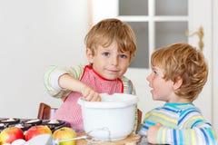 Deux garçons de petit enfant faisant le gâteau aux pommes cuire au four à l'intérieur Photos libres de droits