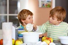 Deux garçons de petit enfant faisant le gâteau aux pommes cuire au four à l'intérieur Photo libre de droits