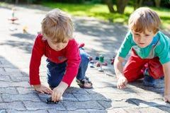 Deux garçons de petit enfant jouant avec des jouets de voiture Image libre de droits