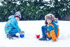 Deux garçons de petit enfant jouant avec la neige dehors Photos libres de droits
