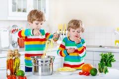 Deux garçons de petit enfant mangeant des spaghetti dans la cuisine domestique Photo stock