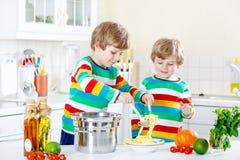 Deux garçons de petit enfant mangeant des spaghetti dans la cuisine domestique Photos stock