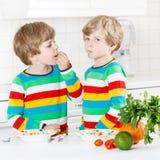 Deux garçons de petit enfant mangeant des spaghetti dans la cuisine domestique Image libre de droits