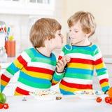 Deux garçons de petit enfant mangeant des spaghetti dans la cuisine domestique Images libres de droits