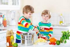 Deux garçons de petit enfant mangeant des spaghetti dans la cuisine domestique Photographie stock libre de droits
