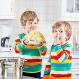 Deux garçons de petit enfant mangeant des spaghetti dans la cuisine domestique Photographie stock
