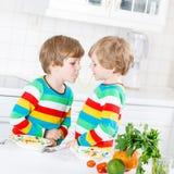 Deux garçons de petit enfant mangeant des spaghetti dans la cuisine domestique Photos libres de droits
