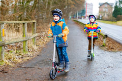 Deux garçons de petit enfant, meilleurs amis montant sur le scooter dans la ville Photo libre de droits