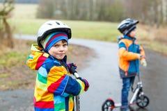 Deux garçons de petit enfant, meilleurs amis montant sur le scooter en parc Photographie stock
