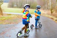 Deux garçons de petit enfant, meilleurs amis montant sur le scooter en parc Image libre de droits