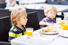 Deux garçons de petit enfant prenant le petit déjeuner sain dans le restaurant d'hôtel Image stock