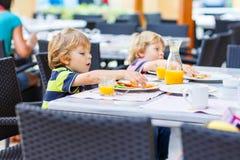 Deux garçons de petit enfant prenant le petit déjeuner sain dans le restaurant d'hôtel Photo libre de droits