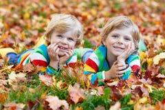Deux garçons de petit enfant s'étendant dans des feuilles d'automne dans l'habillement coloré Photographie stock libre de droits