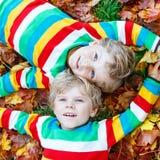 Deux garçons de petit enfant s'étendant dans des feuilles d'automne dans l'habillement coloré Photo libre de droits