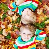 Deux garçons de petit enfant s'étendant dans des feuilles d'automne dans l'habillement coloré Photographie stock