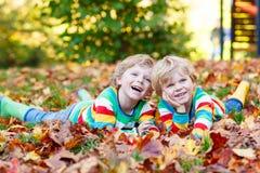 Deux garçons de petit enfant s'étendant dans des feuilles d'automne dans l'habillement coloré Images stock