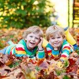 Deux garçons de petit enfant s'étendant dans des feuilles d'automne dans l'habillement coloré Image stock
