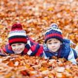 Deux garçons de petit enfant se situant dans des feuilles d'automne, en parc Photos stock