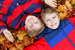 Deux garçons de petit enfant se situant dans des feuilles d'automne dans l'habillement coloré de chute de mode Photo libre de droits