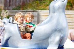 Deux garçons de petit enfant sur le carrousel en parc d'attractions Images libres de droits