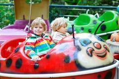Deux garçons de petit enfant sur le carrousel en parc d'attractions Image libre de droits