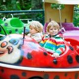 Deux garçons de petit enfant sur le carrousel en parc d'attractions Photo libre de droits