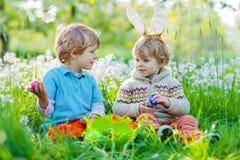 Deux garçons de petit enfant sur Pâques pendant l'oeuf chassent Image libre de droits
