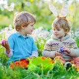 Deux garçons de petit enfant sur Pâques pendant l'oeuf chassent Images stock