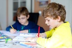 Deux garçons de petits enfants à la maison faisant le travail Images stock