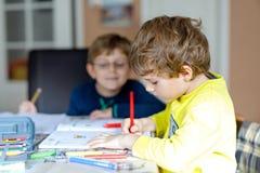 Deux garçons de petits enfants à la maison faisant le travail Photo libre de droits