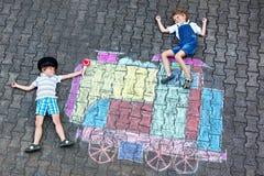 Deux garçons de petits enfants ayant l'amusement avec la photo de craies de train Photographie stock libre de droits