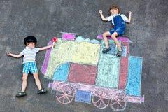 Deux garçons de petits enfants ayant l'amusement avec la photo de craies de train Images stock
