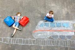 Deux garçons de petits enfants ayant l'amusement avec le dessin de photo de train avec les craies colorées sur la terre Image stock
