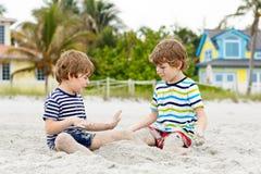 Deux garçons de petits enfants ayant l'amusement sur la plage tropicale Image libre de droits