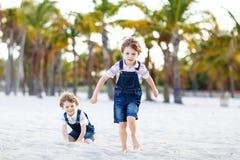Deux garçons de petits enfants ayant l'amusement sur la plage tropicale Images stock