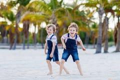 Deux garçons de petits enfants ayant l'amusement sur la plage tropicale Photographie stock